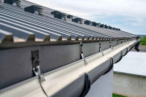 Gutter system for a metal roof. With gutter guards by gold standard restorations the best roofers in mchenry illinois