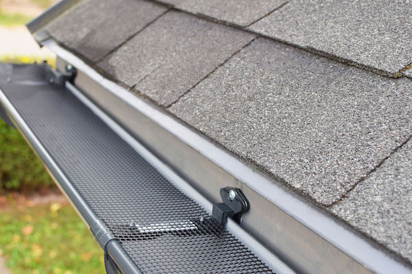 Plastic guard mesh over new dark grey plastic rain gutter on asphalt shingle roof installed by gold standard restorations the best roofers in lake forest illinois