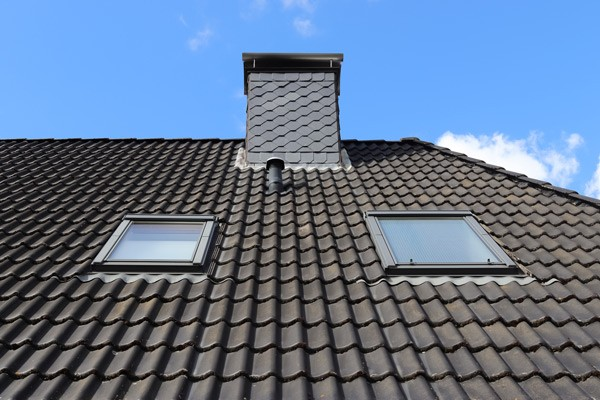 Roof window in velux style with black roof tiles from gold standard restorations the best contractors in elgin for skylight remodeling