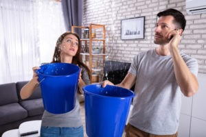 Couple using buckets to catch water leak caused by roof damage from gold standard restorations the best roofers in oak park for 24/7 roof repair - oak park, lombard, aurora, naperville, oak lawn, chicago, illinois
