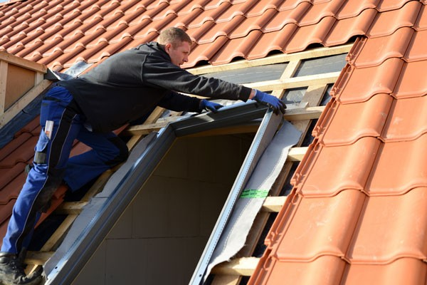 Professional roofer installing skylight into ceramic roof from gold standard restorations the best roofers in woodstock for skylight remodeling