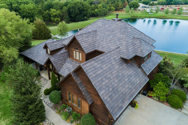 Wooden home on a lake using davinci roofing shingles from gold standard restorations the best roofers in north chicago illinois